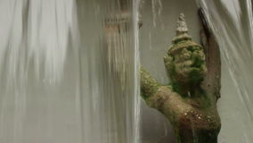 Close up of mythical Garuda figure in Asia seen through the part in a waterfall stock video