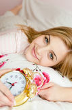 Close up na câmera de sorriso da menina loura encantador bonita da jovem mulher & de vista feliz com um despertador à disposição Fotos de Stock