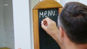 Close-up, na escrita do homem do quadro-negro com giz branco, palavra-menu, suco video estoque