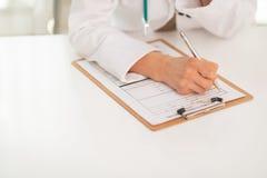 Close up na escrita do médico na prancheta imagens de stock