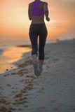 Close up na jovem mulher da aptidão que corre na praia na noite Fotos de Stock