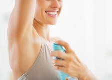 Close up na jovem mulher que aplica o desodorizante sobre underarm imagem de stock royalty free