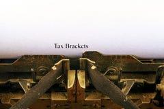 Close up na máquina de escrever do vintage O foco dianteiro nas letras que fazem os SUPORTES de IMPOSTO text Imagem do conceito d imagens de stock