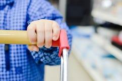 Close up na mão da criança pequena que guarda o trole da compra, casaco azul Fotografia de Stock Royalty Free