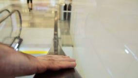 Close up na mão anônima do homem que guarda uma escada rolante que vai para baixo no shopping video estoque
