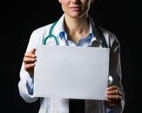 Close up na mulher do doutor que mostra a folha do papel vazio Imagem de Stock