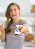 Close up na mulher que come a salada e que olha a tevê Fotografia de Stock Royalty Free