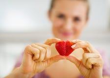Close up na mulher que faz o coração com morango foto de stock