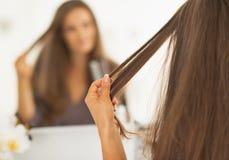 Close up na mulher que verifica o cabelo após o endireitamento Foto de Stock Royalty Free