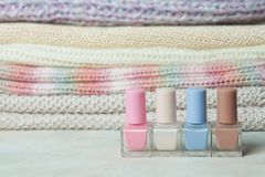 Close up of nail polishes and knitted sweates on background. Pastel colors, beauty fashion winter concept.  Stock Photos