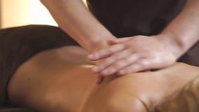 Close-up nas mãos do doutor do homem Mulher que recebe a massagem traseira terapêutica no escritório médico Uma moça recebe a filme