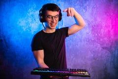 Close-up nas mãos do gamer que vão pressionar uma chave em um teclado O fundo é Lit com luzes de néon fotografia de stock royalty free