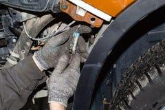 Close-up nas mãos do mestre nas luvas protetoras que conectam o conector com os fios no circuito elétrico do imagem de stock royalty free