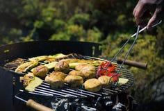 Close-up nas mãos que grelham vegetais no chargrill barbecue Cozinhando vegetais na bandeja da grade em uma marinada da erva, vis fotos de stock royalty free