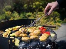 Close-up nas mãos que grelham vegetais no chargrill barbecue Cozinhando vegetais na bandeja da grade em uma marinada da erva, vis imagens de stock royalty free