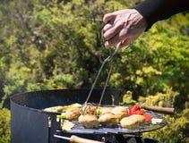 Close-up nas mãos que grelham vegetais no chargrill barbecue Cozinhando vegetais na bandeja da grade em uma marinada da erva, vis imagens de stock