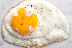 Fried Egg. Close up of a natural looking sunnyside up pan fried egg with salt and coarse ground pepper stock photos