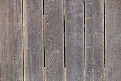 Close-up of natural old vintage weathered gray brown unpainted solid wooden fence or gate of planks and boards. Ecological texture stock image