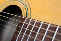 Close up of neck and strings of guitar. Close up of a guitar`s neck, strings, and wood grain - musical instrument Royalty Free Stock Image