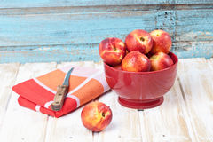 Close up of nectarines in red bowl with napkin and knife Stock Photography