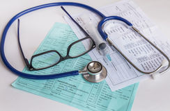 Close up needle syringe and medical stethoscope with glasses on blood chart prescription paper Royalty Free Stock Photography