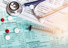 Close up needle syringe and medicine with medical stethoscope on blood chart prescription paper. Selective focus Stock Images