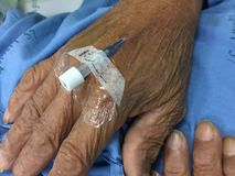 Close up Needles for injection in hand of patient lying. In the hospital bed room Royalty Free Stock Photo