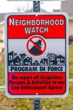Close up of a Neighborhood Watch sign against a blurred background. The sign warns that all suspicious persons and activities are reported to the law royalty free stock photos