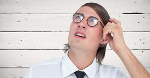 Close up of nerd man scratching head against white wood panel Royalty Free Stock Photography