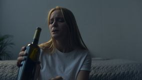 Close up of nervous girl drinking alcohol. Bad day. Close up of young girl feeling frustrated while drinking alcohol and sitting on the floor in her sleeping stock video