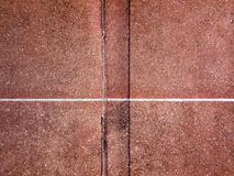 Tennis court from above. Close-up of the net and central line of an old tennis court shot from above Royalty Free Stock Photo