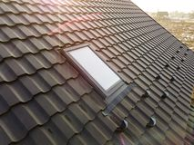 Close-up of new attic plastic window installed in shingled house roof. Professionally done building and construction work, roofing. And installation concept stock photography