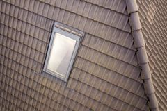 Close-up of new attic plastic window installed in shingled house roof. Professionally done building and construction work, roofing. And installation concept stock photos