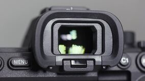 Close up of a new camera vizier isolated on grey background. Action. Viewfinder of a professional photo or video camera.
