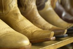 Close-up of new cowboy boots on shelf. Row of new cowboy boots on shelf, close-up Royalty Free Stock Photo