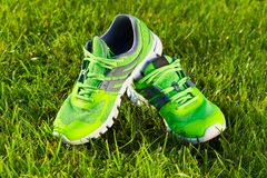 Close up new pairs of green running shoes / sneaker shoes on green grass field in the park stock photo