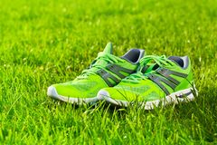 Close up new pairs of green running shoes / sneaker shoes on green grass field in the park royalty free stock photo