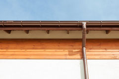 Close up on New Rain Gutter, Downspout, Soffit Board, Fascia Board Installation Against Blue Sky. Royalty Free Stock Photos
