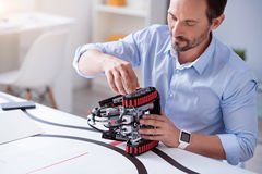 Close up of new robot invention. Repairing process. Concentrated and involved scientist mending his invention Stock Image