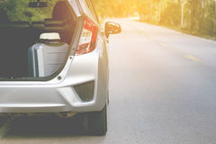 Close up of new silver hatchback car parking on local road with travel luggage Royalty Free Stock Photo