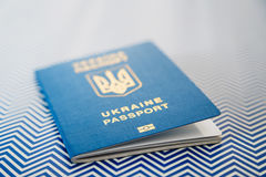 Close up of new ukrainian blue international biometric passport with identification chip on white and blue background. Selective focus Royalty Free Stock Photos