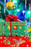 A close-up of a New Year`s gift in a gift box with a bow and a soft blurred background of a dressed up Christmas tree stock photos