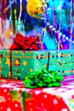 A close-up of a New Year`s gift in a gift box with a bow and a soft blurred background of a dressed up Christmas tree stock images