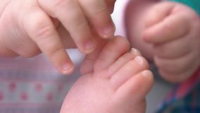 Close up newborn baby feet. Infant baby playing with her feet close up. Babyhood and innocence. Concept of baby development stock video footage