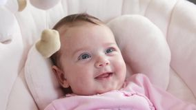 Close up of newborn baby girl smiling in the baby rocker