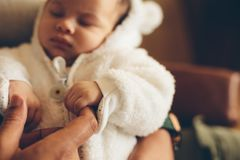 Newborn baby holding father`s finger. Close up of newborn baby holding father`s finger. Boy in his fathers hands Stock Photos