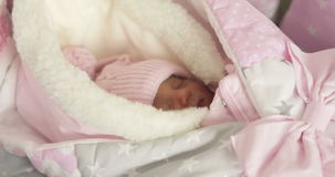 Close-up of a newborn baby in a pink hat and overalls. 4K Close-up of a newborn baby in a pink hat and overalls. Little girl sleeping in the winter suit in the stock video