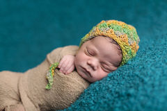 Close up of newborn sleeping. In a green and yellow knit hat Royalty Free Stock Images