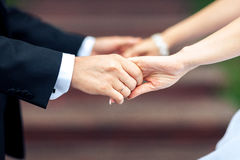 Close-up of newly weds holding each other`s hands and showing their wedding rings royalty free stock photo