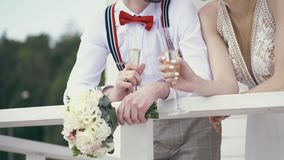 Close-up, newlyweds are holding champagne glasses and a wedding bouquet stock video